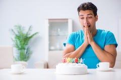 El hombre joven que celebra cumpleaños solamente en casa fotos de archivo