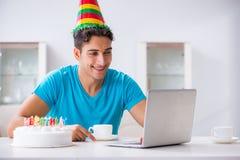El hombre joven que celebra cumpleaños solamente en casa imagen de archivo