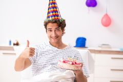 El hombre joven que celebra su cumpleaños en hospital foto de archivo libre de regalías