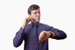El hombre joven que cepilla sus dientes también mira encendido el reloj en el fondo blanco Imágenes de archivo libres de regalías