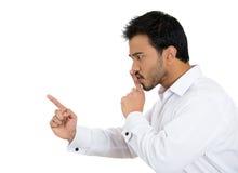 El hombre joven que coloca el finger en los labios para decir el shhhh, sea reservado Fotos de archivo
