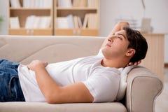 El hombre joven que duerme en sofá del sofá Fotos de archivo libres de regalías