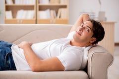 El hombre joven que duerme en sofá del sofá Foto de archivo libre de regalías