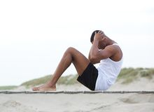 El hombre joven que ejercita en hacer de la playa se sienta sube Foto de archivo
