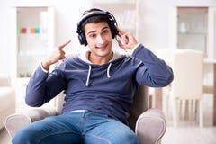 El hombre joven que escucha la música en casa Fotografía de archivo
