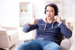 El hombre joven que escucha la música en casa Imágenes de archivo libres de regalías