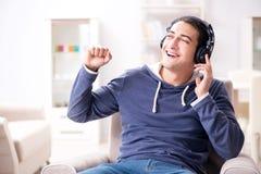 El hombre joven que escucha la música en casa Imagen de archivo