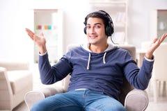 El hombre joven que escucha la música en casa Fotos de archivo libres de regalías