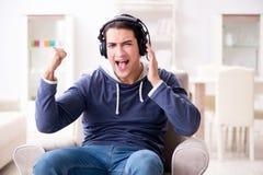 El hombre joven que escucha la música en casa Fotos de archivo