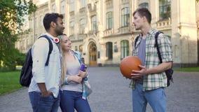 El hombre joven que habla con los pares multirraciales acerca a la universidad, vida despreocupada del estudiante almacen de video