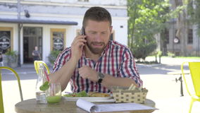 El hombre joven que hablaba por smartphone, durante almuerzo, resbalador tiró a la izquierda metrajes