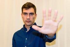 El hombre joven que hacía la muestra de la parada con su mano aumentó la mirada de la cámara foto de archivo