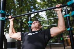 El hombre joven que hace tirón sube en barra horizontal al aire libre, entrenamiento, concepto del deporte Fotografía de archivo