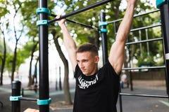 El hombre joven que hace tirón sube en barra horizontal al aire libre, entrenamiento, concepto del deporte Imagen de archivo