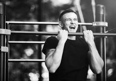 El hombre joven que hace tirón sube en barra horizontal al aire libre, entrenamiento, concepto del deporte Imágenes de archivo libres de regalías