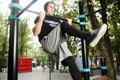 El hombre joven que hace tirón sube en barra horizontal al aire libre, entrenamiento, concepto del deporte Fotografía de archivo libre de regalías