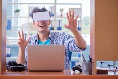 El hombre joven que juega al juego de ordenador con los vidrios de la realidad virtual Foto de archivo
