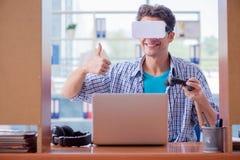 El hombre joven que juega al juego de ordenador con los vidrios de la realidad virtual Imagen de archivo