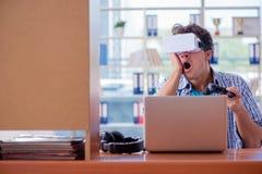 El hombre joven que juega al juego de ordenador con los vidrios de la realidad virtual Fotos de archivo