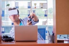 El hombre joven que juega al juego de ordenador con los vidrios de la realidad virtual Imagen de archivo libre de regalías