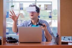 El hombre joven que juega al juego de ordenador con los vidrios de la realidad virtual Foto de archivo libre de regalías