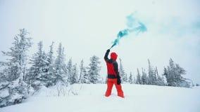 El hombre joven que juega con humo señala por medio de luces en un top de montañas en bosque del invierno almacen de metraje de vídeo