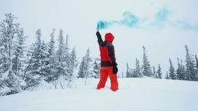 El hombre joven que juega con humo señala por medio de luces en un top de montañas en bosque del invierno metrajes