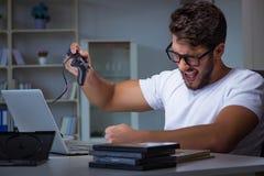 El hombre joven que juega las largases horas de los juegos atrasadas en la oficina fotos de archivo libres de regalías
