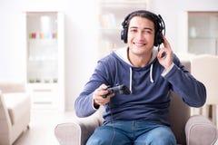 El hombre joven que juega a los juegos de ordenador en casa Foto de archivo