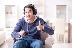 El hombre joven que juega a los juegos de ordenador en casa Imágenes de archivo libres de regalías