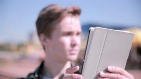 El hombre joven que juega Pokemon ENTRA en la ciudad, usando la tableta almacen de metraje de vídeo