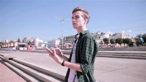 El hombre joven que juega Pokemon ENTRA en la ciudad, usando la tableta almacen de video