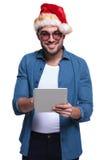 El hombre joven que lleva el sombrero de santa está trabajando en una tableta Fotografía de archivo libre de regalías