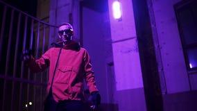 El hombre joven que lleva la chaqueta y las gafas de sol rojas enérgico canta en la noche metrajes