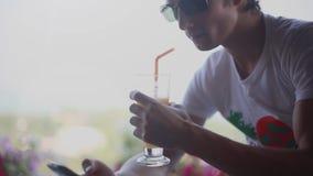 El hombre joven que lleva las gafas de sol utiliza el teléfono móvil y el cóctel de consumición en jardín en café 1920x1080 almacen de video
