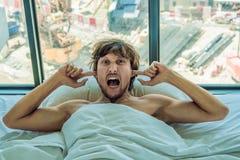 El hombre joven que mentía en una cama cubrió sus oídos debido al ruido En la ventana después de la cama usted puede ver la const fotos de archivo libres de regalías