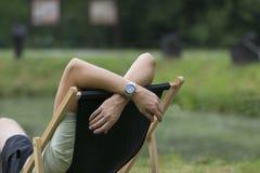 El hombre joven que miente en un deckchair en el jardín, se relaja, día libre imágenes de archivo libres de regalías