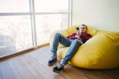 El hombre joven que miente en una silla amarilla del bolso cerca de una ventana panorámica grande y utiliza el teléfono Rotura qu Imagen de archivo