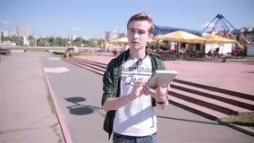 El hombre joven que mira el mapa en su tableta, jugando Pokemon ENTRA en la ciudad metrajes