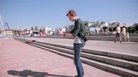 El hombre joven que mira el mapa en su tableta, jugando Pokemon ENTRA en la ciudad almacen de video