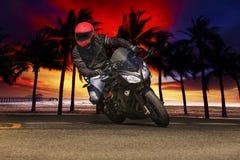 El hombre joven que monta la motocicleta grande de la bici en las carreteras de asfalto contra sea Foto de archivo