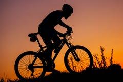 El hombre joven que monta una bici en la puesta del sol Fotos de archivo