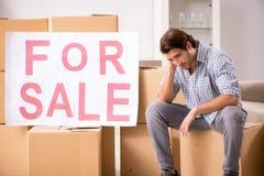 El hombre joven que ofrece a casa en venta y que se mueve hacia fuera imágenes de archivo libres de regalías