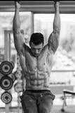 El hombre joven que realiza la pierna de la ejecución aumenta ejercicio del ABS fotos de archivo