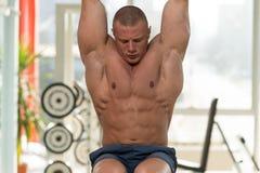 El hombre joven que realiza la pierna de la ejecución aumenta ejercicio del ABS foto de archivo libre de regalías