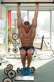 El hombre joven que realiza la pierna de la ejecución aumenta ejercicio del ABS fotografía de archivo