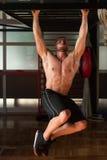 El hombre joven que realiza la pierna de la ejecución aumenta ejercicio del ABS imágenes de archivo libres de regalías
