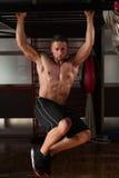 El hombre joven que realiza la pierna de la ejecución aumenta ejercicio del ABS imagen de archivo