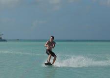 El hombre joven que se agacha Wakeboarding en el ` s de Aruba riega Fotos de archivo libres de regalías