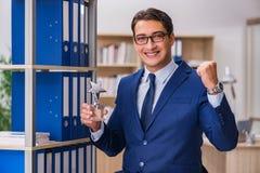 El hombre joven que se coloca al lado del estante con las carpetas Imagen de archivo libre de regalías